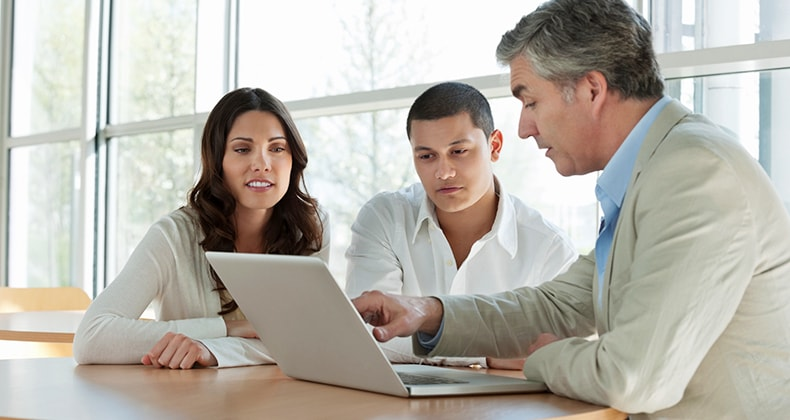 adviser-showing-laptop-screen-to-couple-client-mst